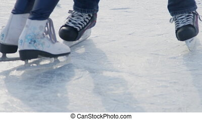 Close-up legs of couple skating on frozen water outdoors in...