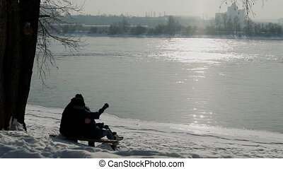 Couple sit on bench admiring reflection of sun rays in river in winter.