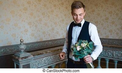 Handsome man posing indoor. European groom look to the...