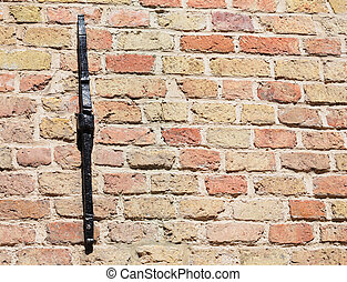 Old pastel brick wall with black painted metal buttress