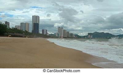 Waves on a Beach under Highrise Buildings of Nha Trang,...