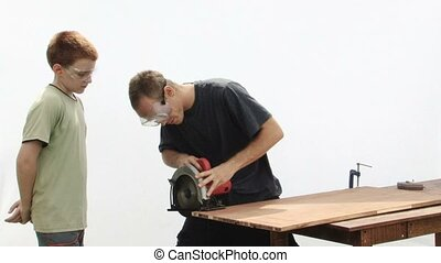Cutting Wood - Construction worker teaching a teenage boy...