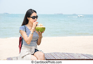 Girl with coconut on a beach - Girl drinking fresh coconut...