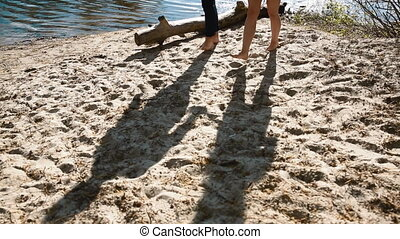 Couple walking on the beach. Long shadow on the sand with no...