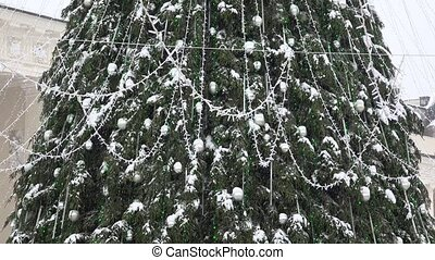 Big Christmas tree with silver toys and lights in heavy snowstorm snow falling