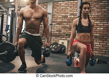 Young couple working out with kettlebells