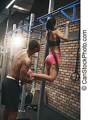 Personal trainer helping woman with pull ups