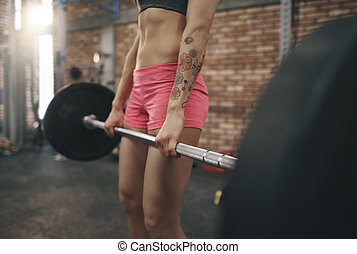 Female legs while lifting a barbell