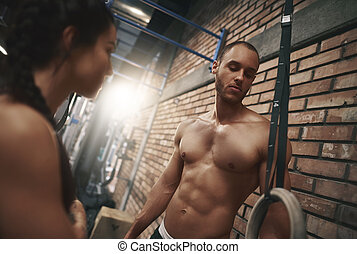 Man focused before workout on gymnastic rings