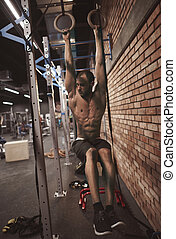 Strong body of man on gymnastic rings