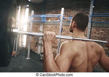 Rear view of man with a barbell