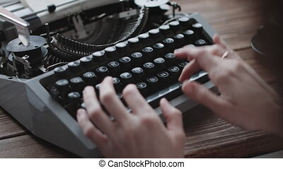 Writer typing with retro writing machine. View from over...