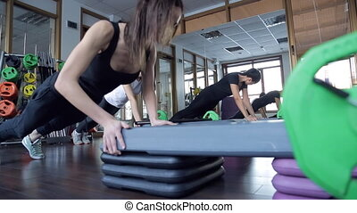 Trainer with her group of women push-up from special benches...