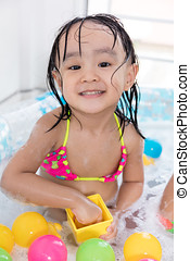 Happy Asian Chinese little girl playing in the inflatable pool