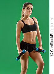 Young attractive woman with dumbbells in her hands posing in...