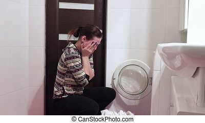 Loading of laundry in the washing machine - Brunette girl...