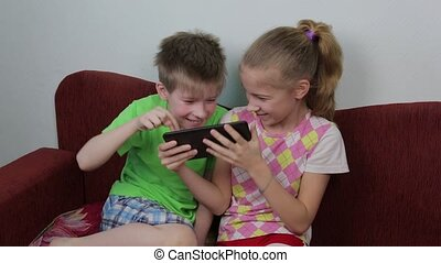 Happy brother and sister playing tablet