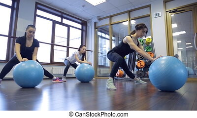 Trainer with her group of women do exercises with blue fitboll in gym.