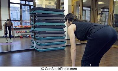 Brunette sportswoman do deadlift using 5 kilo blue dumbbells...