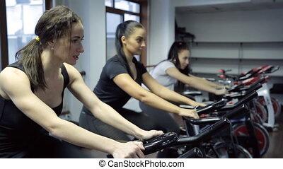Tree women do exercises on exercise bike in fitness center.