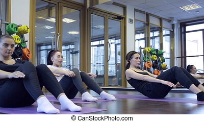 Group of women with trainer rock press on mat in fitness...