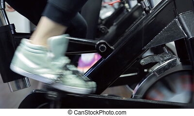 two pairs of feet twist exercise bicycle pedal in fitness center.