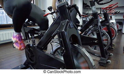 Two women pedaling exercise bike in gym. Only legs. In...