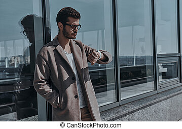 Just in time. Confident young man in eyewear checking the...