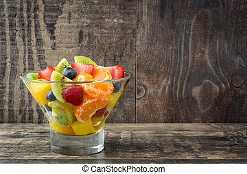 Fruit salad in crystal bowl on white wooden table.Copyspace
