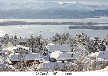 Snowy houses in a white winter landscape in western Norway.