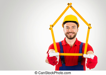 home improvement - handyman with house shaped ruler in hands on gray background with copy space