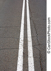 Texture of an asphalt road with a top view of a double white...