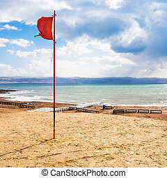 red flag on beach on Dead Sea in winter season - Travel to...