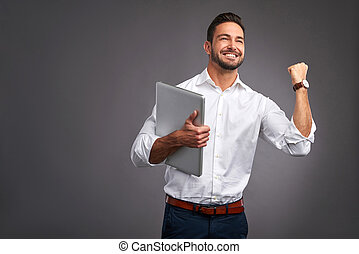 Young man with laptop - A happy handsome young man holding a...