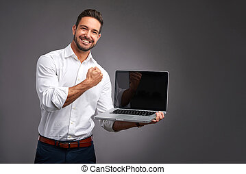 Young man with laptop - A handsome young man holding and...