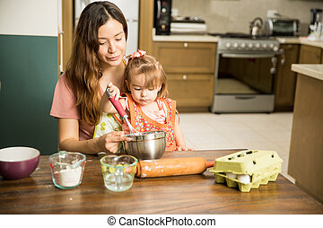 Mom mixing flour with her daughter