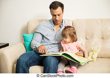 Young father and daughter reading - Handsome Latin father...
