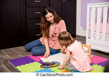 Mother and her child painting in the nursery