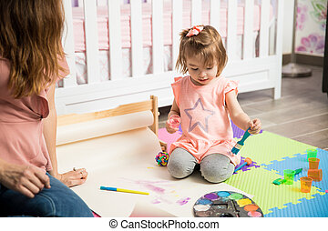 Cute toddler painting next to her mom