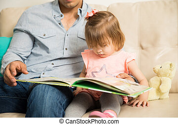 Pretty little girl reading with her father - Closeup of a...