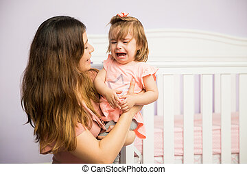 Mom calming down her crying daughter - Gorgeous Hispanic...