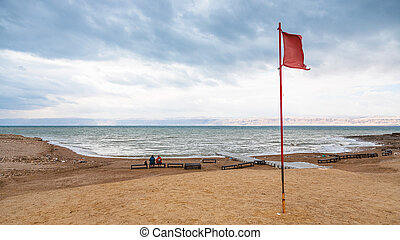 red flag on beach of Dead Sea in winter