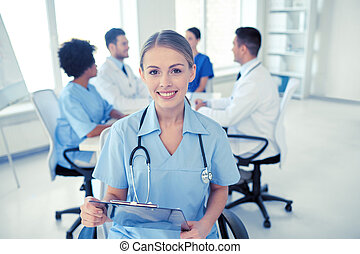 happy doctor with clipboard over group of medics - health...