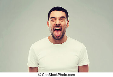 man showing his tongue over gray background - expression,...