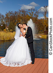The groom tenderly kisses the bride in the neck standing on...