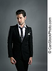 Fashion young businessman black suit casual tie on gray...