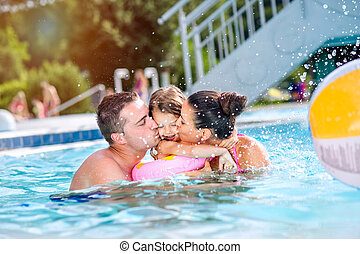Mother, father kissing daughter in swimming pool. Sunny...