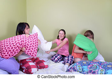 Teen pillow fight - Three teenage girls in their pajamas...