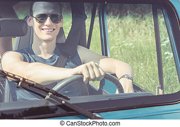 Young man driving car during sunny day