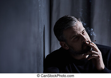 Man smoking a cigarette - Sad middle-aged man smoking...